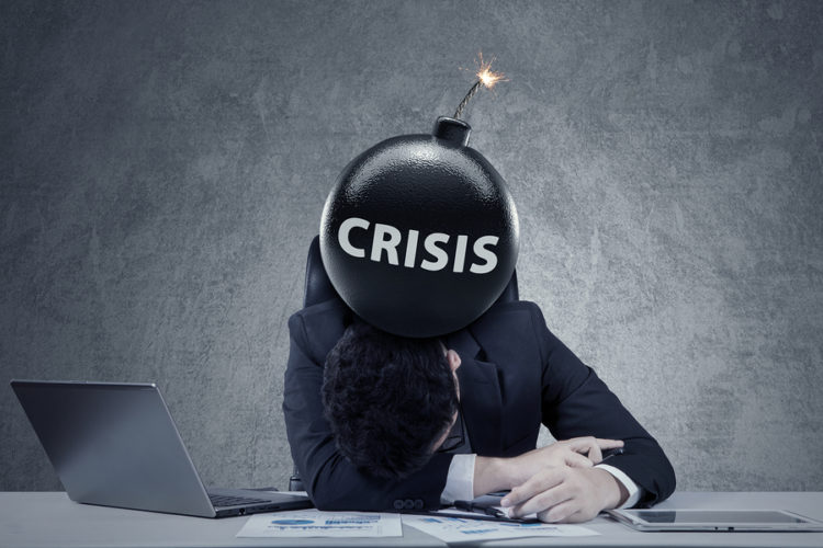 Frustrated Entrepreneur Sleeping On The Table With A Bomb Of Financial Crisis On His Head. Concept Of Bankruptcy And Financial Crisis